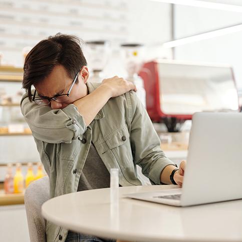 man sneezing into elbow